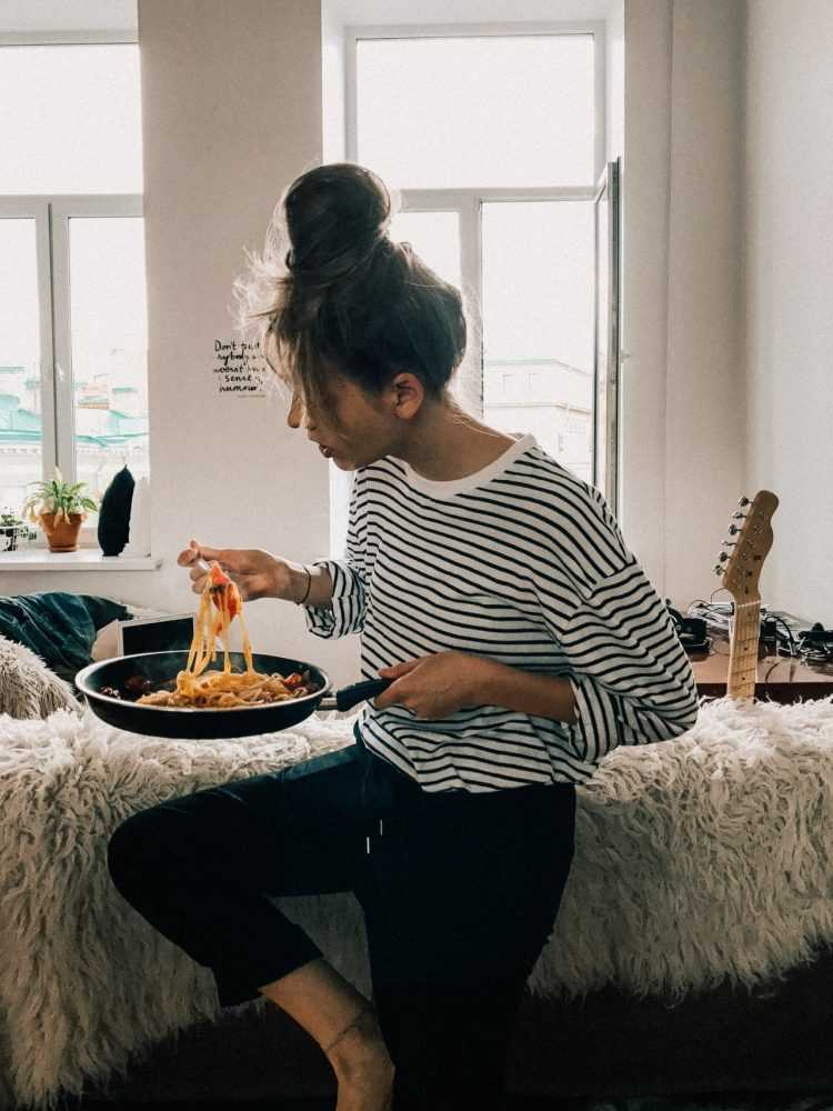 woman-in-black-and-white-striped-shirt-eating-food-from-pot
